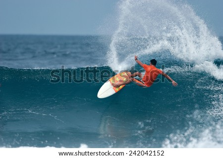 A surfer throws a huge plume of spray as he executes a radical cutback. - stock photo