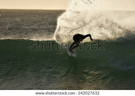 A surfer throws up a huge plume of spray in the dawn light. - stock photo
