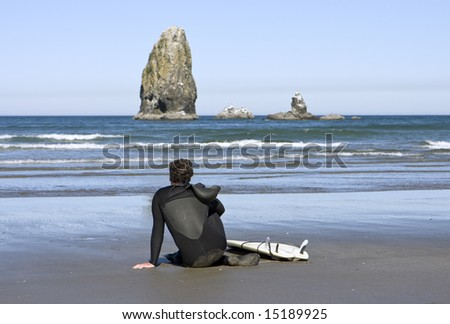 A surfer waiting for the right waves is scanning the ocean horizon while resting on a sandy beach. The seastack in the distance is just off Cannon Beach in Oregon. - stock photo