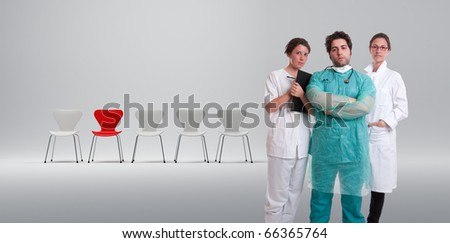 A surgeon and his team with a row of white chairs and a red one - stock photo