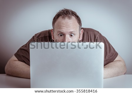 A surprised man with wide eyes sits hidden behind a laptop notebook computer staring at the screen with a shocked or frustrated expression on his face. - stock photo