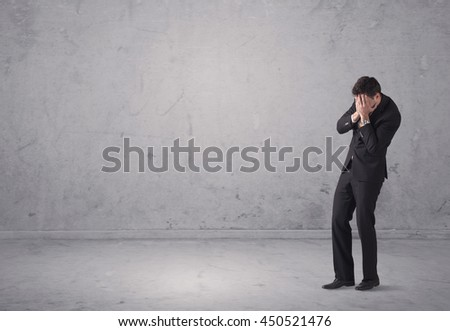 A surprised young sales person in elegant suit standing in empty urban environment with grey concrete wall background concept - stock photo