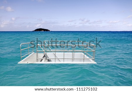 A surreal image of a concrete staircase access to an underground chamber in the middle of a vast ocean. - stock photo
