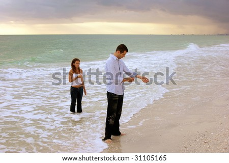 A surreal image of young couple coming out of the ocean fully dressed at sunset. The man is fixing his shirt