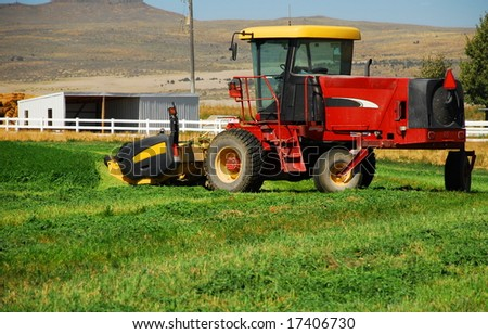 A swather sits in a half - harvested field of alfalfa.
