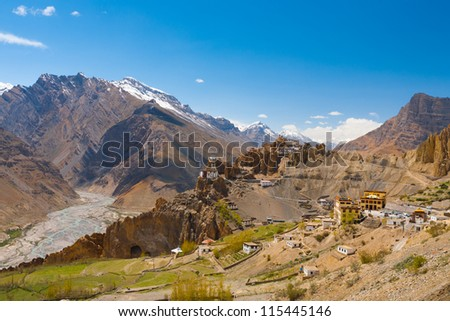 A sweeping wide view of the Spiti Valley and Himalaya mountains behind the stunning old and new Monastery of Dhankar, Himachal Pradesh, India - stock photo