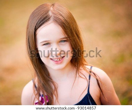 A sweet adorable brunette young girl outdoors smiles for a portrait. - stock photo