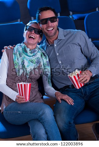 A sweet couple watching a 3d movie and enjoying with each other in movie theater.
