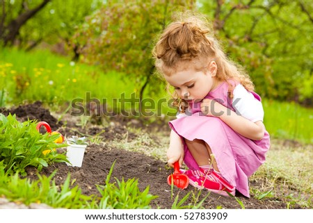 A sweet curly girl in the garden - stock photo