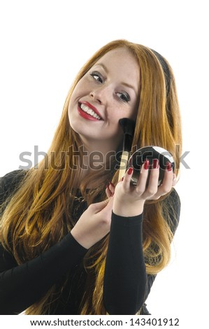 A sweet girl with long reddish hair and a black dress wearing Rouge with a large brush on their cheeks while smiling and looking into a mirror, isolated against white background.