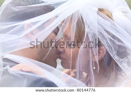 A sweet kiss. Bride and groom at the wedding - stock photo