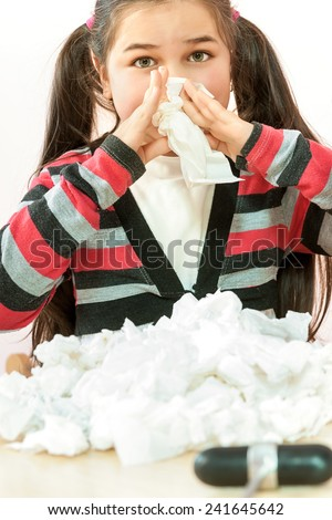 A sweet little girl sneezing into a tissue while her pediatrician sits and looks on worriedly - stock photo