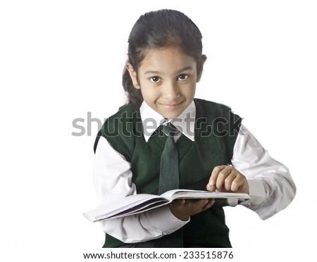 A sweet school girl taking teacher,s note from blackboard - stock photo