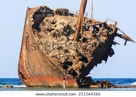 A swimmer stands next to a huge, rusting shipwreck on a tropical coral reef - stock photo