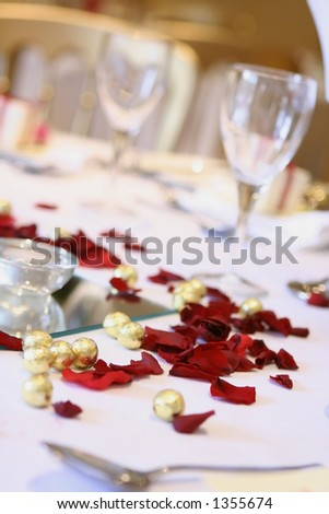 A table arrangement at a wedding reception with scattered chocolate balls, rose petals and wine glasses