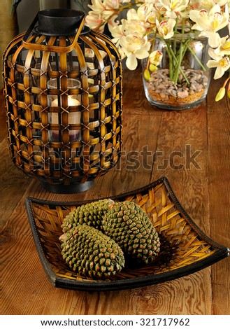 a table close up with decorative accessories (candle,vase,pines,dish - stock photo