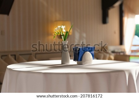 A table covered with a white tablecloth. On the table in a white vase is a white flower with in napkins. - stock photo
