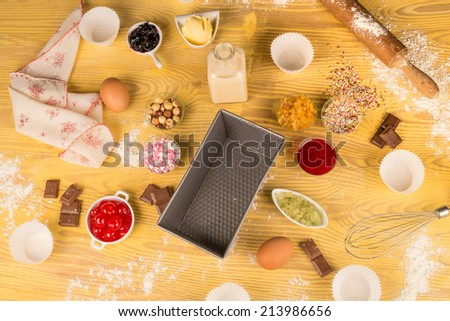 A table full of ingredients and objects for homemade baking - stock photo