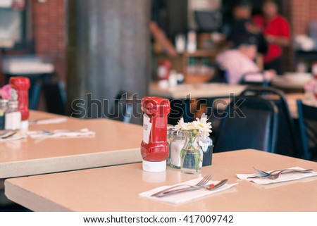 A Table in a Fast Food Cafe Served with a Ketchup Bottle - stock photo
