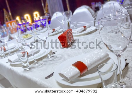 a table in the restaurant, the white tablecloth and plates, forks and knifes, glasses, napkins,