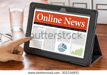 A tablet computer on a desk - Online News - stock photo