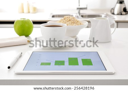 a tablet computer showing some charts and an apple, a cup of coffee and a bowl with cereals on the kitchen table - stock photo