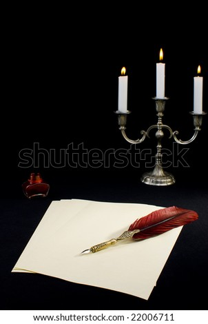 A tabletop with writing feather and candles - stock photo