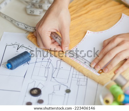 A tailor is laying out a dress/Sewing layout. Soft focus  - stock photo