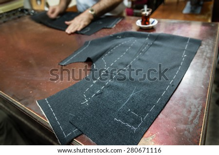 A tailor's work table with  cloth for a jacket cut and marked up for sewing. (SELECTIVE FOCUS) - stock photo