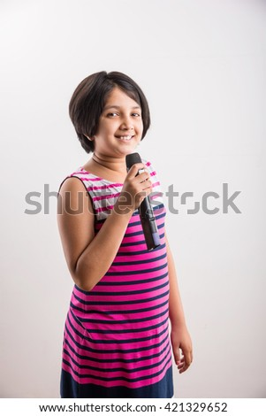 A talented little Indian girl singing on mic, on white studio background.  lovely asian girl holding a black wireless microphone and singing