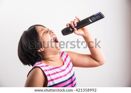 A talented little Indian girl singing on mic, on white studio background.  lovely asian girl holding a black wireless microphone and singing - stock photo