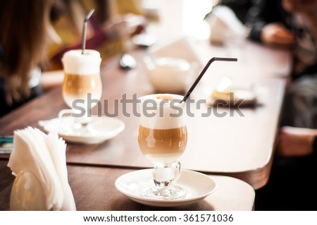 A tall glass containing latte coffee standing on a wooden table in cafe