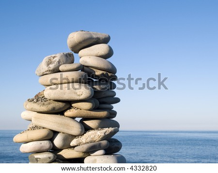 A tall pile of rocks stacked on the beach - stock photo
