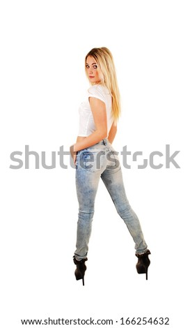 A tall slim young blond woman in jeans and white top standing from the back for white background.