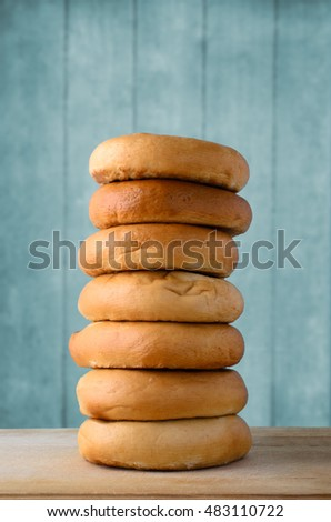 A tall stack of whole bagels, on a light wooden chopping board with a turquoise blue plank background.
