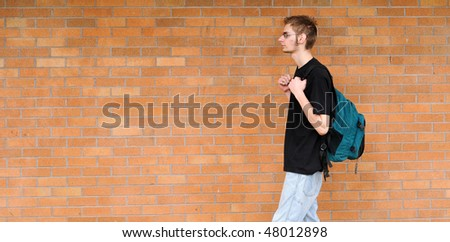 A tall white Caucasian young adult teenage male walks in front of a brick wall. Lots of room for your copyspace text. He has a backpack and glasses - stock photo