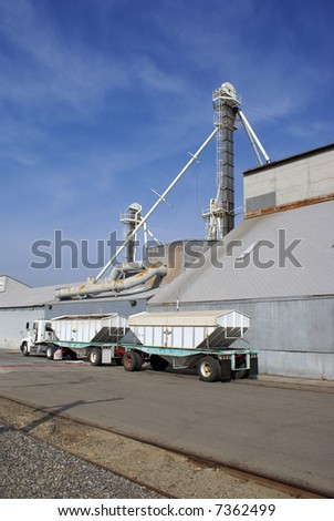 A tandem trailer truck rig awaits loading at a fertilizer plant - stock photo