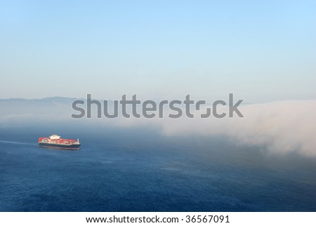A tanker carrying containers flowing into the fog.