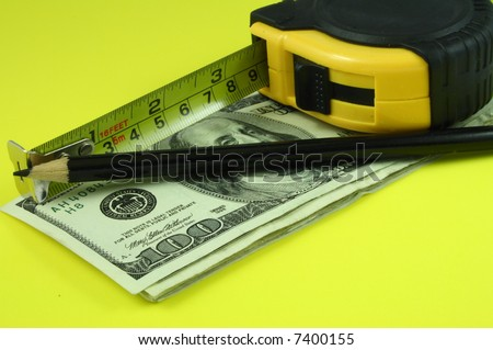a tape measure and a black pencil over several bills of one hundred dollars - stock photo