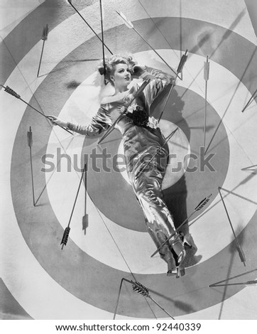 A target of desire, a young woman lying on the bulls eye with arrows around her