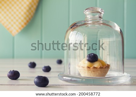 A tartlet with blueberries and pastry cream on a glass bell jar. Several blueberries on a white wooden table with a robin egg blue background and a yellow checkered napkin. Vintage Style. - stock photo