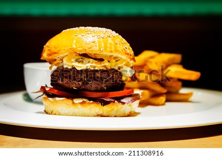 A tasty beef burger with blue cheese at the nice club restaurant. - stock photo