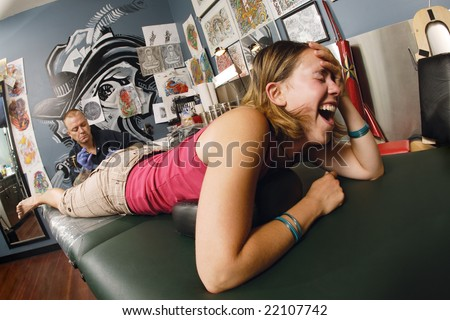 A tattoo artist applying his craft onto the lower leg of a pain-inflicted female. Property release supplied includes tattooists' wall mural and drawings posted on the walls behind him. - stock photo