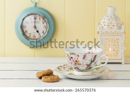 A tea cup decorated with flowers, two biscuits and a candle on a white wooden table. In the background a turquoise clock on a yellow wainscot. Vintage tea time - stock photo