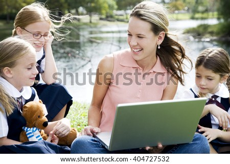A teacher and children using a laptop outside - stock photo