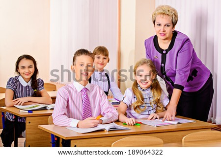 A teacher and her students during class at school. Education. - stock photo