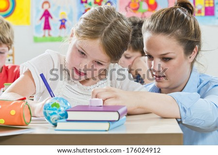 A teacher helping one of her students with work.