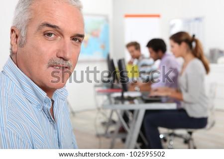 A teacher in his classroom - stock photo
