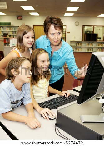 A teacher instructing kids on using the computer. - stock photo