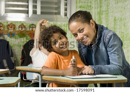 A teacher with a student in a classroom.  They are facing the camera and are smiling. Horizontally framed shot. - stock photo